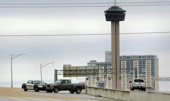 A San Antonio police vehicle pushes a stranded pickup off of I 37 south bound near the I 10 exit ramp, on Friday, Jan. 24, 2014.  The truck had spun out as it crossed the icy overpass. Photo: BOB OWEN, San Antonio Express-News / © 2012 San Antonio Express-News
