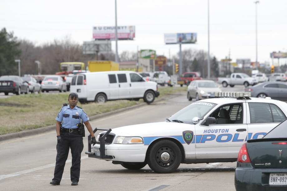 A HPD police officer directs traffic along the feeder of westbound Hwy. 290 near Fairbanks North Houston Road as other vehicles work to move off the freeway Friday, Jan. 24, 2014, in Houston. (Melissa Phillip / Houston Chronicle)