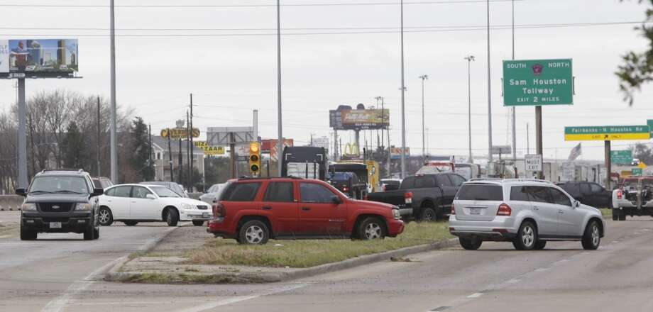 Vehicles work to move off westbound Hwy. 290 near Fairbanks North Houston Road. Traffic was backed up due to being diverted from the main lanes to the feeder roads to avoid the icy overpasses Friday, Jan. 24, 2014, in Houston. (Melissa Phillip / Houston Chronicle)