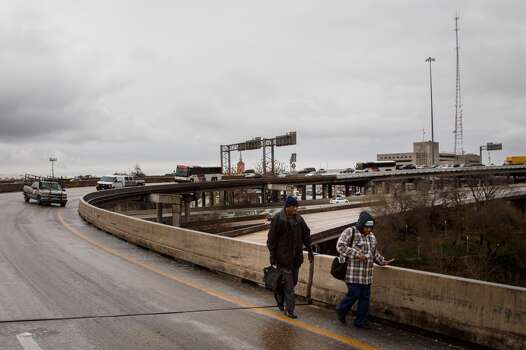 Passengers of a Houston Metro bus elect to walk down the icy McKinney St. exit ramp off of I-45 after being stranded on the bus for 2hrs due to icy road conditions, Friday, Jan. 24, 2014, in Houston. ( Michael Paulsen / Houston Chronicle ) Photo: Michael Paulsen, Houston Chronicle