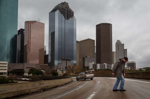 Rusty Rouse tries to walk up an ice-slicked McKinney St. exit ramp after he and other motorists became stranded due to ice road conditions, Friday, Jan. 24, 2014, in Houston. ( Michael Paulsen / Houston Chronicle ) Photo: Michael Paulsen, Houston Chronicle