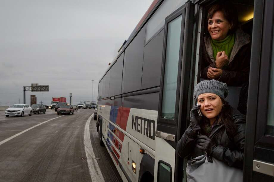 Norma Ortega, top, and Debora Walker look outside from a Metro Bus headed to downtown after becoming stranded for over 2hrs. on the McKinney St. exit ramp off of I-45 due to icy road conditions that snarled the morning commute, Friday, Jan. 24, 2014, in Houston. ( Michael Paulsen / Houston Chronicle ) Photo: Michael Paulsen, Houston Chronicle
