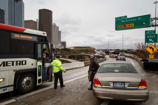 Riogo Rodriguez, right, gets help from Byron Foulks, center, after becoming stranded for over 2hrs. on the McKinney St. exit ramp off of I-45 due to icy road conditions that snarled the morning commute, Friday, Jan. 24, 2014, in Houston. ( Michael Paulsen / Houston Chronicle ) Photo: Michael Paulsen, Houston Chronicle