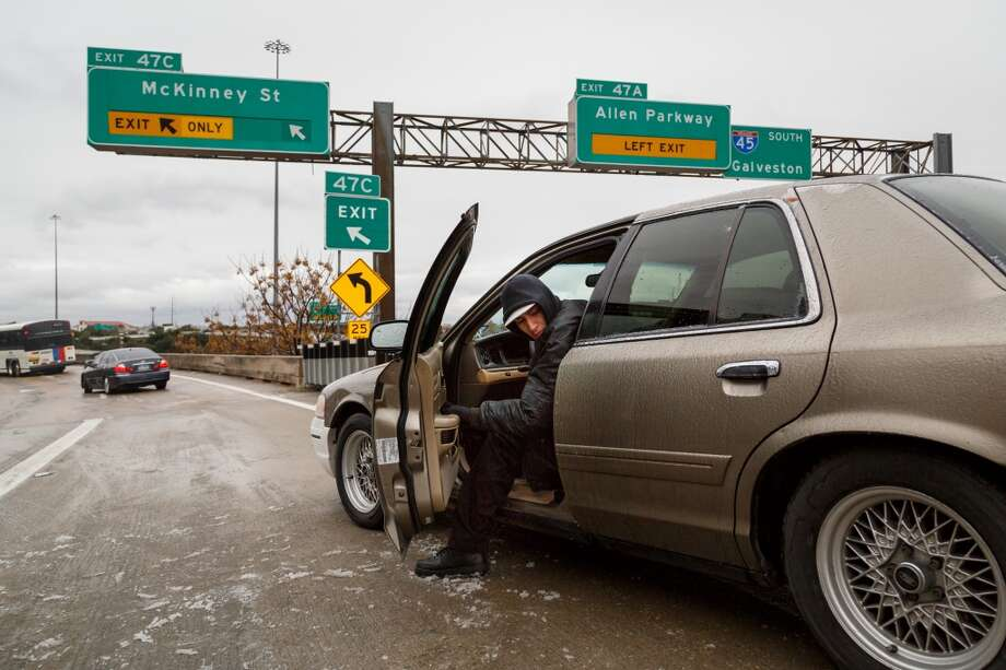 Riogo Rodriguez tries to back his car out after becoming stranded for over 2hrs. on the McKinney St. exit ramp off of I-45 due to icy road conditions that snarled the morning commute, Friday, Jan. 24, 2014, in Houston. ( Michael Paulsen / Houston Chronicle ) Photo: Michael Paulsen, Houston Chronicle