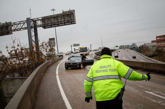 Byron Foulks helps a motorist who was stranded for over 2hrs. on the McKinney St. exit ramp off of I-45 due to icy road conditions that snarled the morning commute, Friday, Jan. 24, 2014, in Houston. ( Michael Paulsen / Houston Chronicle ) Photo: Michael Paulsen, Houston Chronicle