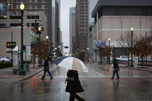 Pedestrians cross the street along Preston where icy road conditions snarled the morning commute, Friday, Jan. 24, 2014, in Houston. ( Michael Paulsen / Houston Chronicle ) Photo: Michael Paulsen, Houston Chronicle