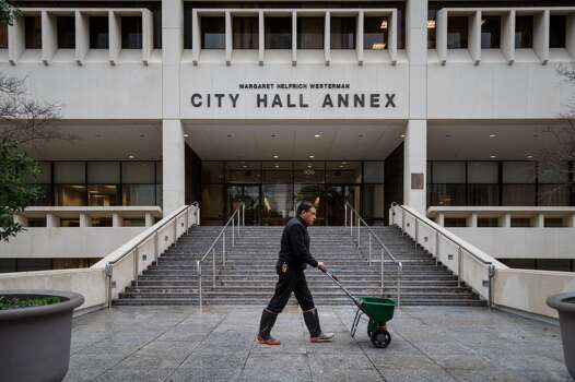 Martin Contreras puts melting salt in front of the City Hall Annex as icy cold road conditions snarled the morning commute, Friday, Jan. 24, 2014, in Houston. ( Michael Paulsen / Houston Chronicle ) Photo: Michael Paulsen, Houston Chronicle