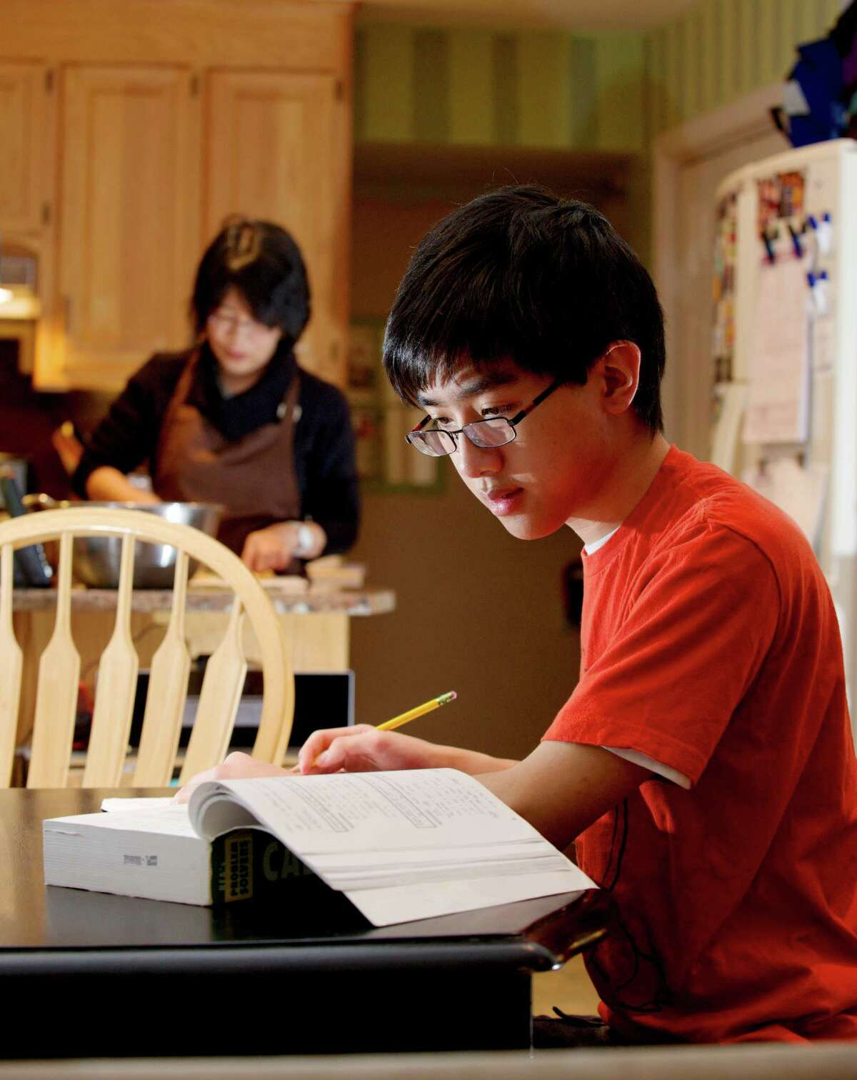 Howard Ho, 18, works on his calculus while his mother Sandy Ho prepares dinner in their New Milford, Conn, home. Ho is home schooled and has been applying to colleges for the fall. He has already started taking classes at Western Connecticut State University. Tuesday, January 14, 2014.