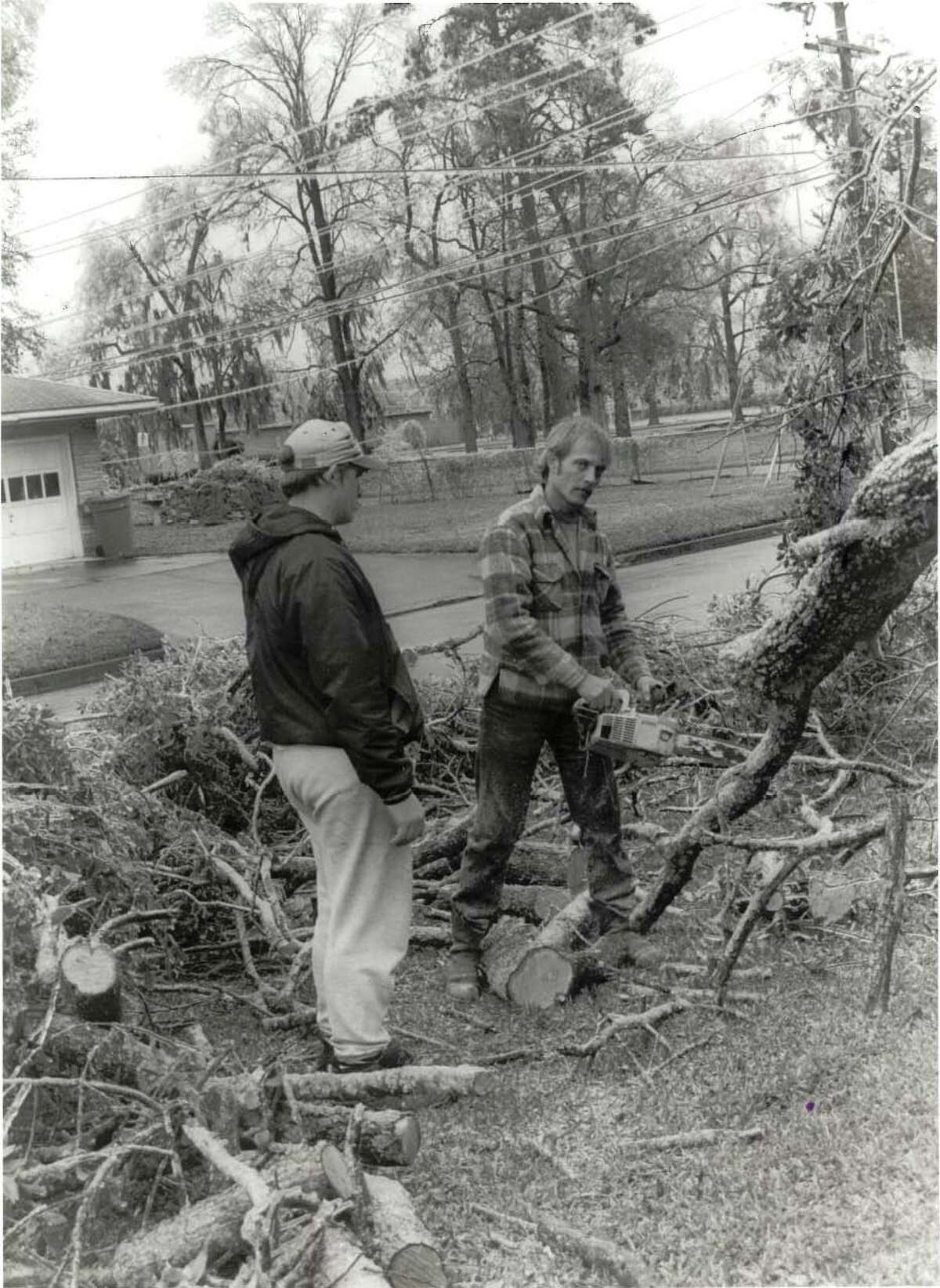 Jason Lisenby, left, and Jimmie Dyson, co-owner of Goodwin's Tree Service, cut downed branches at 19th and North Streets.