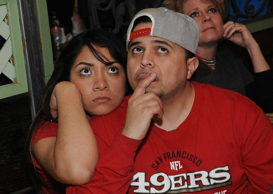 In distress - Gris Gomez (left) and Joshua Topete watch last Sunday's Niners-Seahawks game and don't appear to be happy about it. Photo: Susana Bates, Special To The Chronicle