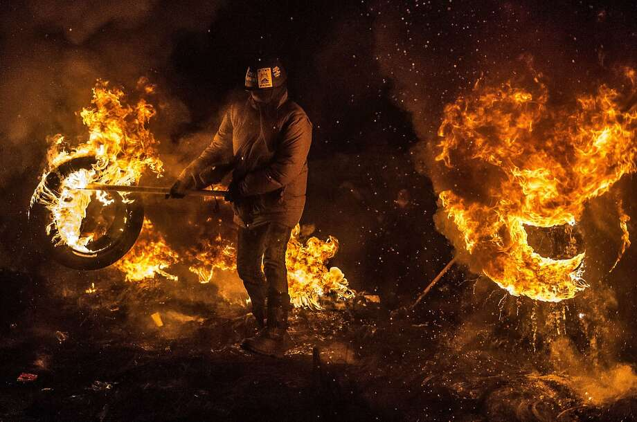 Antigovernment protesters burn tires and warm themselves at a barricade in downtown Kiev. Photo: Dmitry Serebryakov, AFP/Getty Images