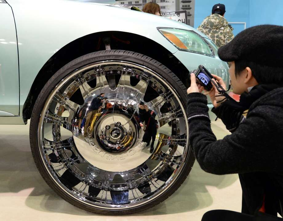 A visitor takes a picture of Lexus GS430's 32-inch wheel with 305/25R32 tire at the Nextworks WHIPS booth during the Tokyo Auto Salon 2014 exhibition at the Makuhari Messe in Chiba. Photo: TOSHIFUMI KITAMURA, AFP/Getty Images