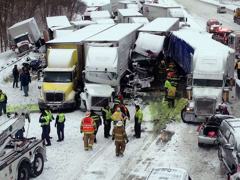 Deadly mess in Indiana: Emergency crews work the scene of a massive pileup involving more than 40 vehicles, many of them tractor-trailers, along Interstate 94 near Michigan City. At least three people were killed and more than 20 injured. Photo: Uncredited, Associated Press