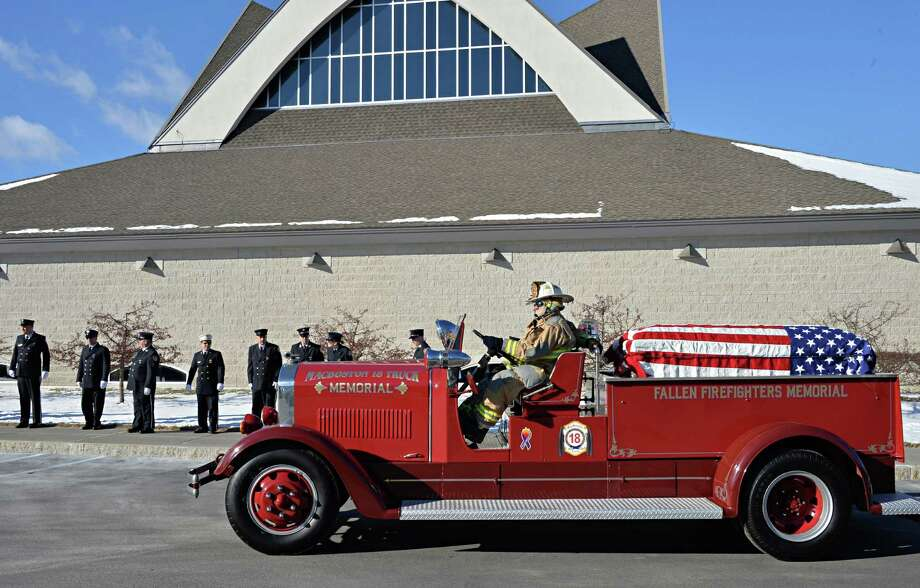 A flag-draped casket carrying the body of long-time member of the Jonesville Volunteer Fire Department, Louis Pasquarell Sr. arrives for funeral services aboard a 1936 fire truck at Corpus Christi Church Friday Jan. 24, 2014, in Clifton Park, NY.  A 77-year member of the department, Pasquarell would have driven this exact truck when it was in service in Jonesville.  (John Carl D'Annibale / Times Union) Photo: John Carl D'Annibale / 00025497A