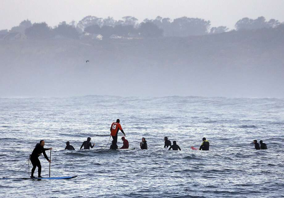 A man paddleboards, left, past a group of surfers waiting to catch a wave in the first heat of the first round of the Mavericks Invitational big wave surf contest Friday, Jan. 24, 2014, in Half Moon Bay, Calif.  Photo: Eric Risberg, Associated Press
