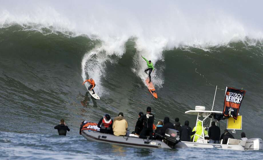 Shane Dorian, left, and Ben Wilkinson, right, catch a wave during the third heat of the first round of the Mavericks Invitational big wave surf contest Friday, Jan. 24, 2014, in Half Moon Bay, Calif. Photo: Eric Risberg, Associated Press