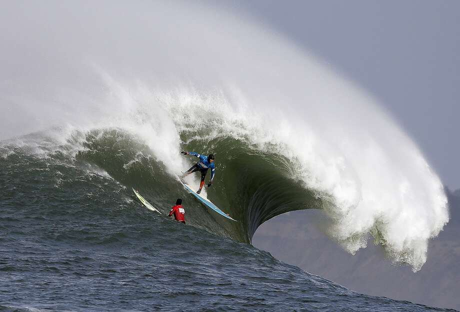 Peter Mel catches a wave as Colin Dwyer, below, is near during the second heat of the first round of the Mavericks Invitational big wave surf contest Friday, Jan. 24, 2014, in Half Moon Bay, Calif. Mel is the defending champion of the event. (AP Photo/Eric Risberg) Photo: Eric Risberg, Associated Press