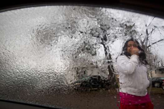Elizabeth Villanueva stands outside her car while waiting for ice to melt from the windshield Friday, Jan. 24, 2014, in Houston. ( Brett Coomer / Houston Chronicle ) Photo: Brett Coomer, Houston Chronicle