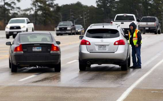 Tow truck driver Deric Lopez helps a motorist stuck due to icy conditions on the Louetta bridge at I-45 North Friday, Jan. 24, 2014, in Spring. ( Brett Coomer / Houston Chronicle ) Photo: Brett Coomer, Houston Chronicle