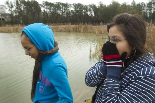 Gabby Uceda, left, and her sister, Juliana, bundle up against the cold as they walk along the pond at Creekside Park Friday, Jan. 24, 2014, in The Woodlands. Classes in Conroe ISD schools were cancelled Friday due to icy weather.  ( Brett Coomer / Houston Chronicle ) Photo: Brett Coomer, Houston Chronicle