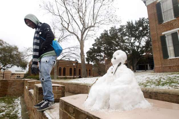 David Grant, of Houston, walks past a small snowman shaped like a seated Sam Houston in front of Austin Hall on the campus of Sam Houston State University following an overnight snowfall Friday, Jan. 24, 2014, in Huntsville. Classes at SHSU were cancelled Friday. ( Brett Coomer / Houston Chronicle ) Photo: Brett Coomer, Houston Chronicle