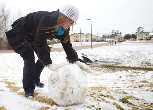 Christina Rizer, a Sam Houston State University senior from Spring, rolls a ball of snow to make a snowman following an overnight snowfall Friday, Jan. 24, 2014, in Huntsville. Classes at SHSU were cancelled Friday. ( Brett Coomer / Houston Chronicle ) Photo: Brett Coomer, Houston Chronicle
