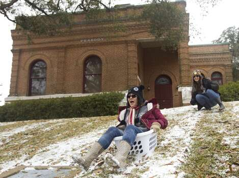 Brittany Munoz, left, slides down a hill after a push from Jeimmy Tellez in front of the Peabody Library in a laundry basket following an overnight snowfall on the campus of Sam Houston State University Friday, Jan. 24, 2014, in Huntsville. Classes at SHSU were cancelled Friday. ( Brett Coomer / Houston Chronicle ) Photo: Brett Coomer, Houston Chronicle