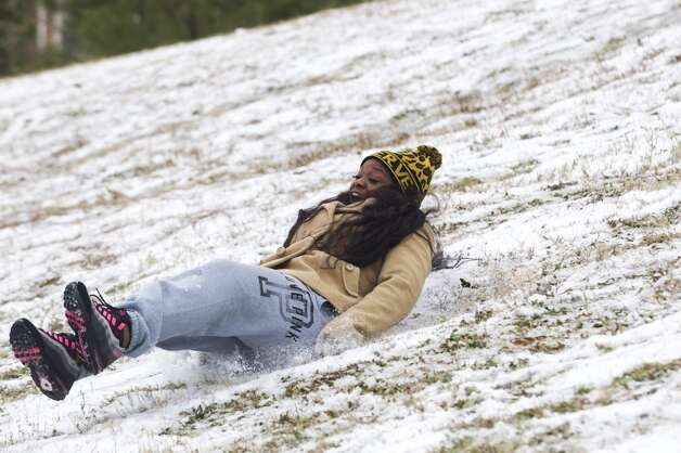 Sam Houston State University student Marissa Anukwuem, of Houston, slides down a snow-covered hill following an overnight snowfall Friday, Jan. 24, 2014, in Huntsville. Classes at SHSU were cancelled Friday. ( Brett Coomer / Houston Chronicle ) Photo: Brett Coomer, Houston Chronicle