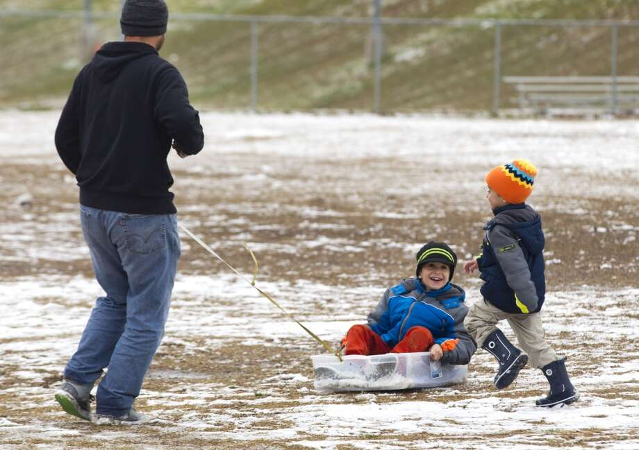 Buiar Haidini, left, pulls his son, Orges, in a plastic tub around a field of snow on the campus of Sam Houston State Univeristy, with Riad Haidini running alongside, following an overnight snowfall Friday, Jan. 24, 2014, in Huntsville. Haidini, who lives in the Willowbrook area of Houston, brought his sons to Huntsville so they could see snow for the first time. ( Brett Coomer / Houston Chronicle ) Photo: Brett Coomer, Houston Chronicle