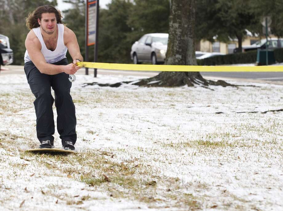 """Michael Vogel, of Spring, is pulled on a skim board along a field of snow on the campus of Sam Houston State University following an overnight snowfall Friday, Jan. 24, 2014, in Huntsville. Classes at SHSU were cancelled Friday. """"You don't get too many snow days,"""" Vogel said. """" You have to make the best of them."""" ( Brett Coomer / Houston Chronicle ) Photo: Brett Coomer, Houston Chronicle"""