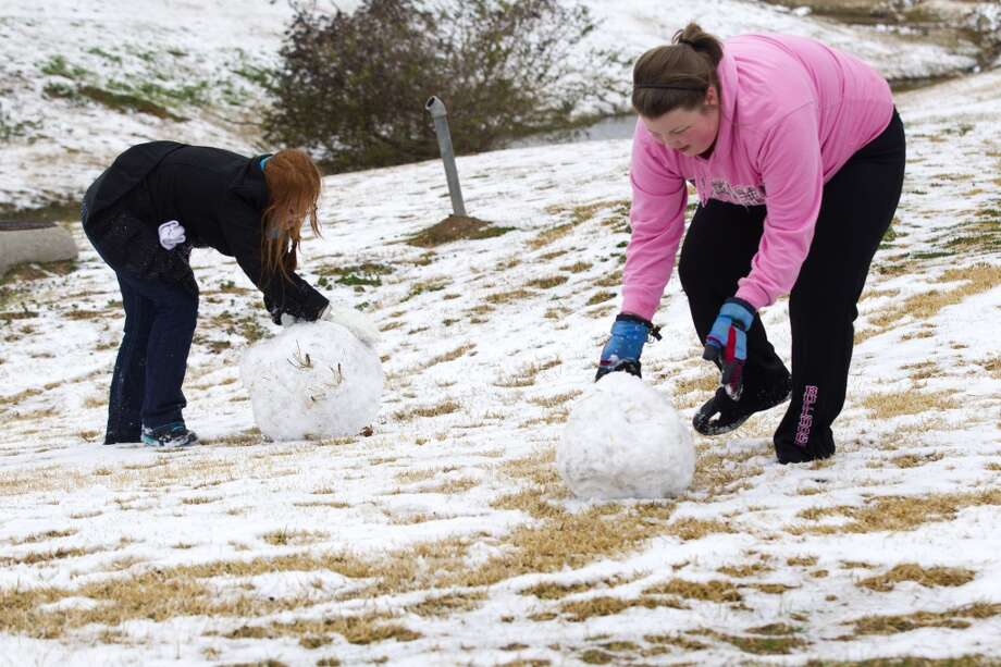 Christina Rizer, a Sam Houston State University senior from Spring, left, and Haley Griffin, of Carthage, work on making a snowman following an overnight snowfall Friday, Jan. 24, 2014, in Huntsville. Classes at SHSU were cancelled Friday. ( Brett Coomer / Houston Chronicle ) Photo: Brett Coomer, Houston Chronicle