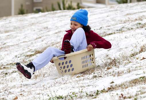 Sam Houston State University student Andrea Gonzales, of Houston, slides down a snow-covered hill in a laundry basket following an overnight snowfall Friday, Jan. 24, 2014, in Huntsville. Classes at SHSU were cancelled Friday. ( Brett Coomer / Houston Chronicle ) Photo: Brett Coomer, Houston Chronicle