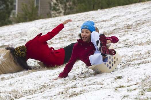 Sam Houston State University student Andrea Gonzales, of Houston, crashes as she slides down a snow-covered hill in a laundry basket following an overnight snowfall Friday, Jan. 24, 2014, in Huntsville. Classes at SHSU were cancelled Friday. ( Brett Coomer / Houston Chronicle ) Photo: Brett Coomer, Houston Chronicle