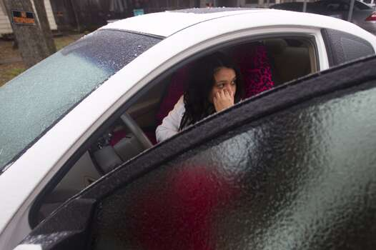 Elizabeth Villanueva sits in her car while waiting for ice to melt from the windshield Friday, Jan. 24, 2014, in Houston. A light freezing rain and sleet left freeway overpasses and bridges ice-covered and slippery Friday. Traffic was lighter than usual, but numerous traffic wrecks were reported. ( AP Photo/Houston Chronicle, Brett Coomer) Photo: Brett Coomer, Associated Press