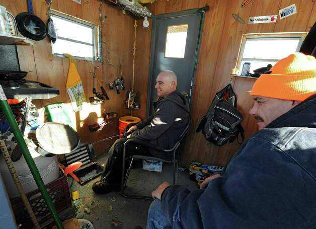 Jack Sullivan, left, and Shawn Baker, both of Warrensburg, stay warm while ice fishing in Sullivan's ice shanty on Lake George Friday, Jan. 24, 2014 in Bolton Landing, N.Y. The men are seasonal workers who do construction in the good weather and have time to fish in the winter months. (Lori Van Buren / Times Union) Photo: Lori Van Buren