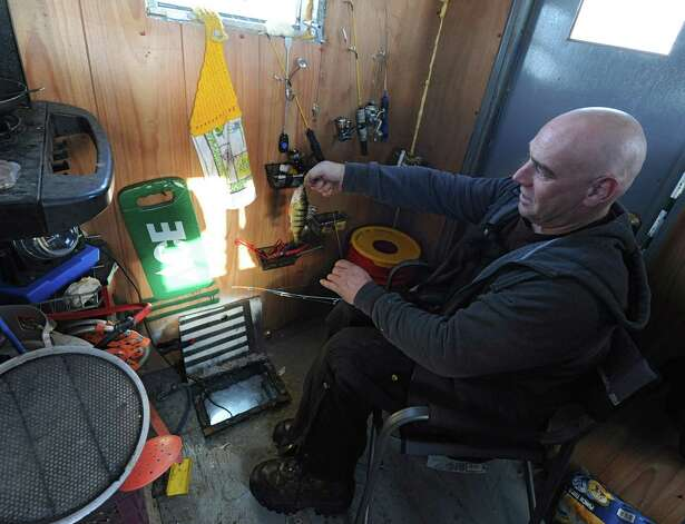 Jack Sullivan of Warrensburg catches a yellow perch in his ice shanty on Lake George Friday, Jan. 24, 2014 in Bolton Landing, N.Y. Sullivan is a seasonal worker who does construction in the good weather and has time to fish in the winter months. (Lori Van Buren / Times Union) Photo: Lori Van Buren