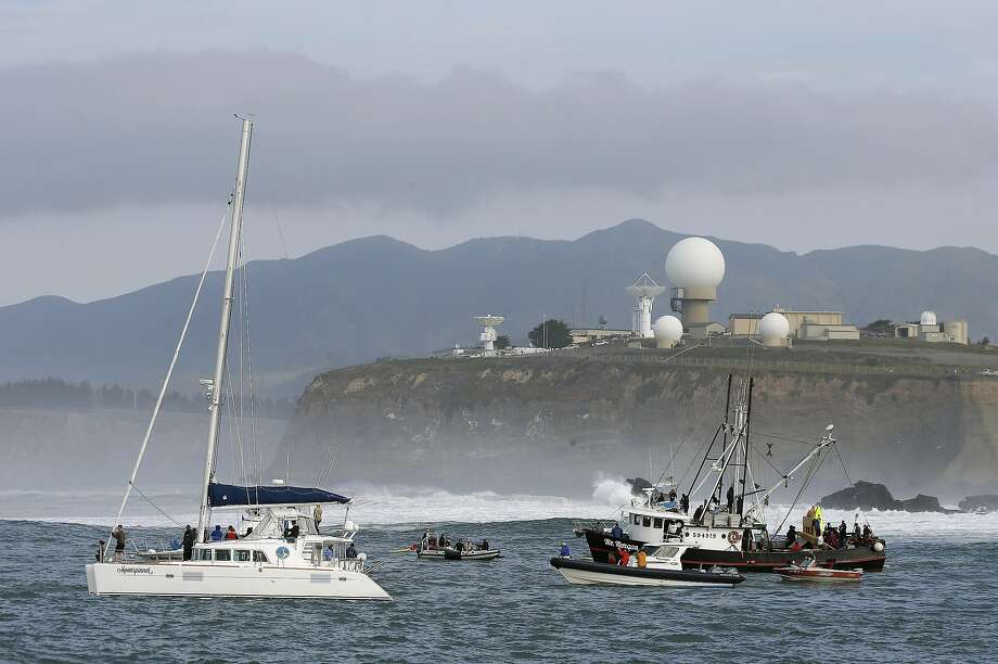People on boats watch the third heat of the first round of the Mavericks Invitational big wave surf contest with the Pillar Point Air Force Station in the background Friday, Jan. 24, 2014, in Half Moon Bay, Calif. Photo: Eric Risberg, Associated Press