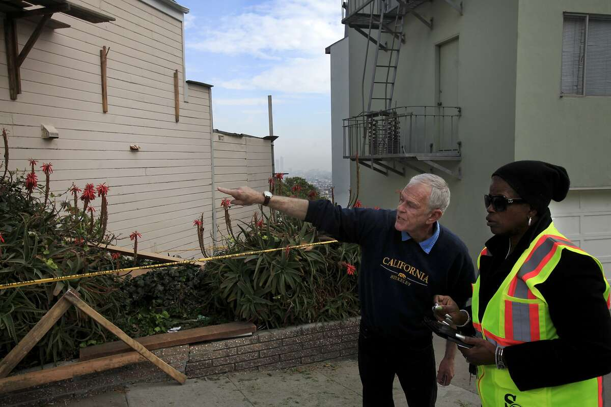 Neighbor Chris Smith, left, recounts a scaffolding accident he heard to a San Francisco Department of Public Works employee that happened on the house at left Jan. 24, 2014 at a house under construction near Eureka Valley in San Francisco, Calif. Three construction workers sustained non-life-threatening injuries when their scaffolding collapsed under their combined weight and they fell over 15 feet to the ground below.
