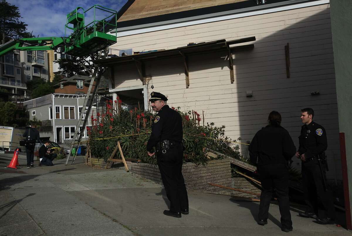 Police officers, including Officer Mike Caplan, center, stand at the scene of a scaffolding accident Jan. 24, 2014 at a house under construction near Eureka Valley in San Francisco, Calif. Three construction workers sustained non-life-threatening injuries when their scaffolding collapsed under their combined weight and they fell over 15 feet to the ground below.