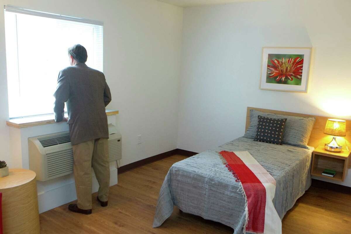 New Hope board president Michael M. Fowler looks out the window at Rittenhouse, a low-income complex with 160 dormlike rooms.