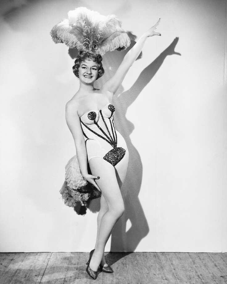 Full length portrait of Joan Sims (1930-2001), British actress, wearing a showgirl costume with a feather headdress in a studio portrait, against a white background, circa 1965. Photo: Silver Screen Collection, Getty Images
