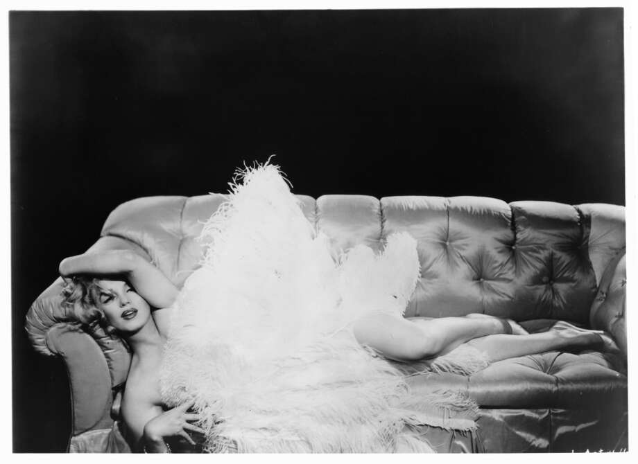 Marilyn Monroe lying on her side on an over stuffed sofa with large feathers covering her in a scene from the film 'The Prince And The Showgirl', 1957. Photo: Michael Ochs Archives, Getty Images