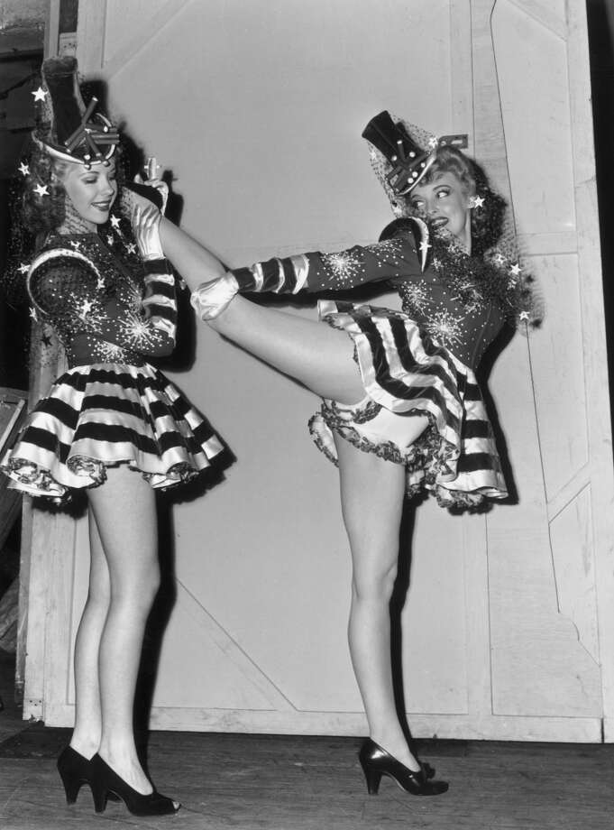 circa 1943:  EXCLUSIVE A full-length image of a showgirl stretching her leg back on another showgirl's shoulder as they warm-up backstage for a performance of the Hollywood Group Caravan, a group of celebrities who toured thirteen US cities to raise funds for the Army and Navy relief effort during World War II. The dancers are wearing American-flag inspired costumes covered in stars, stripes, and lace. Their tops hats are decorated with firecracker bouquets. Photo: Gene Lester, Getty Images