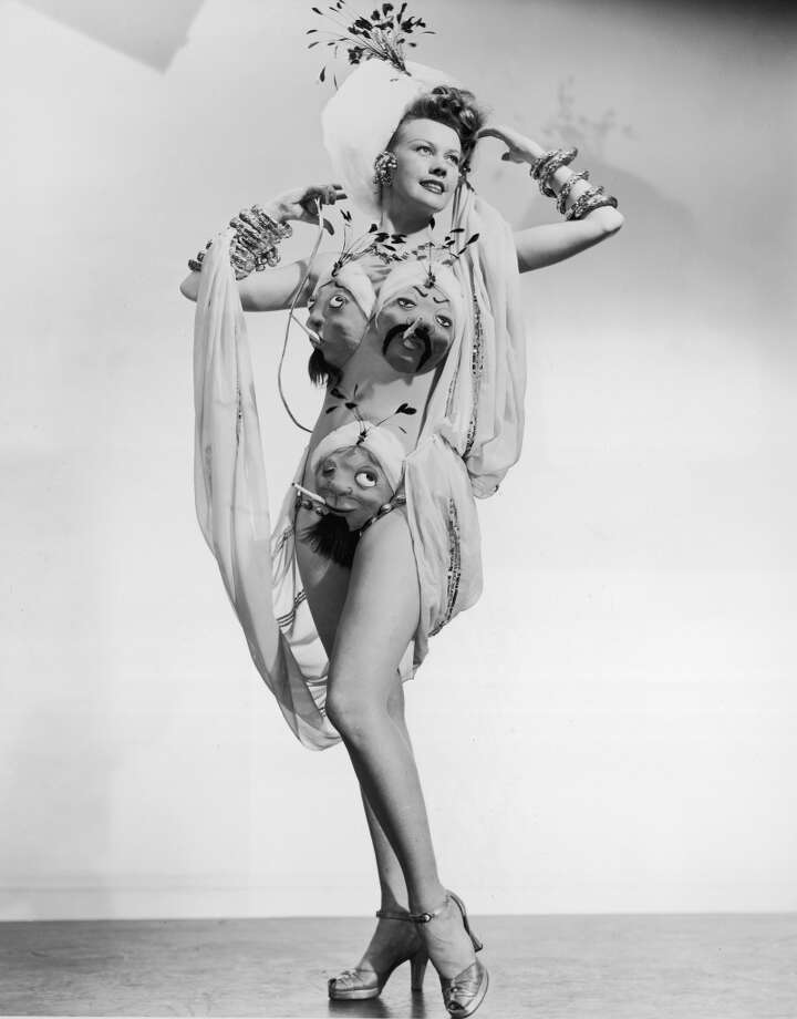 circa 1945:  Full-length portrait of a showgirl wearing a burlesque costume consisting of inflatable Middle Eastern men's faces smoking cigarettes. Photo: Hulton Archive, Getty Images