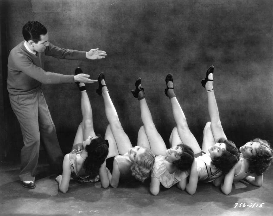circa 1932:  A troupe of dancers limber up under the guidance of dance director Earl Lindsay, in preparation for a scene in the Paramount film 'Backstage Blues', directed by Mack & Moran. Photo: Margaret Chute, Getty Images