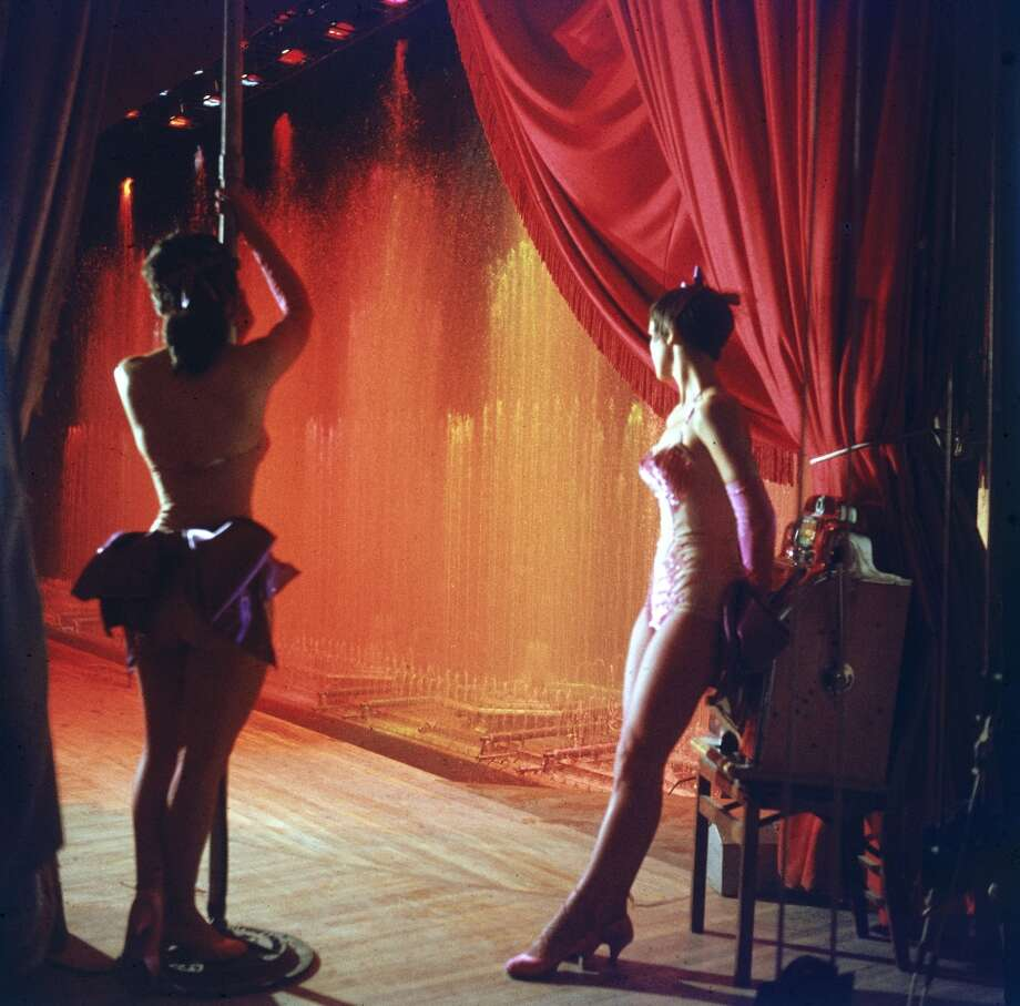 Two show girls stand in the wings during a performance at the Royal Nevada Hotel, Las Vegas, Nevada, 1955. One leans against a portable slot machine. Photo: Loomis Dean, Time & Life Pictures/Getty Image