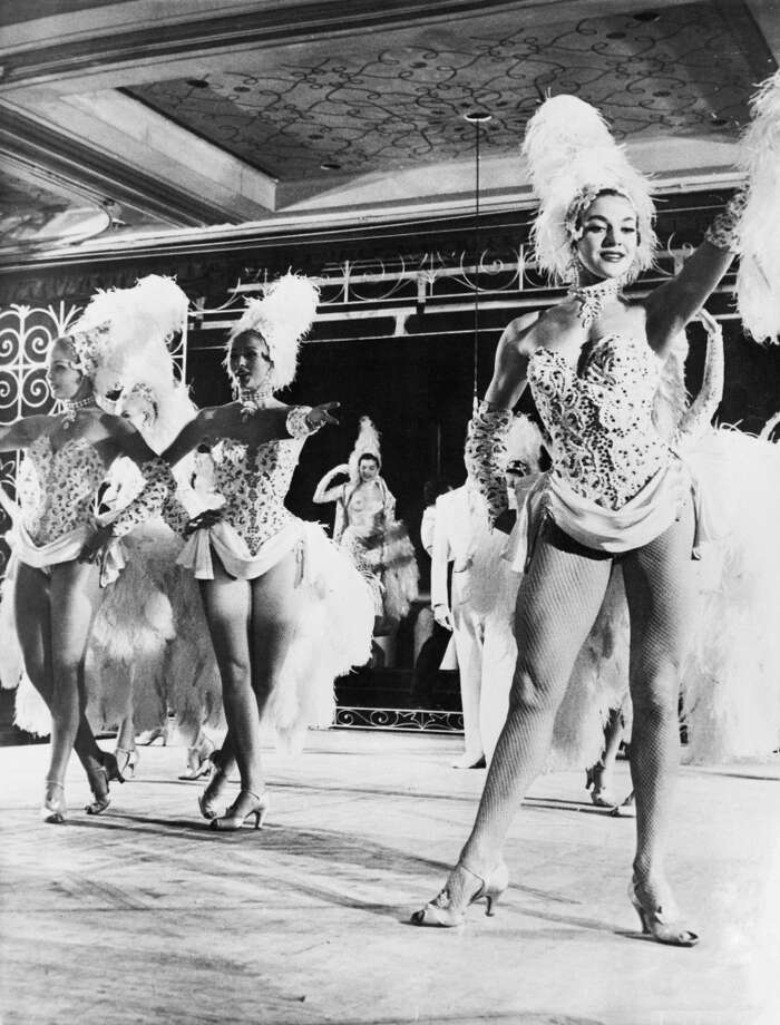 Showgirl Molly Dexter (right) on stage at the Lido in Paris with the Bluebell Girls, 25th May 1957. Molly, who weighed just over 10 stone, was recently sent home to Sheffield to put on more weight. Photo: Express, Getty Images