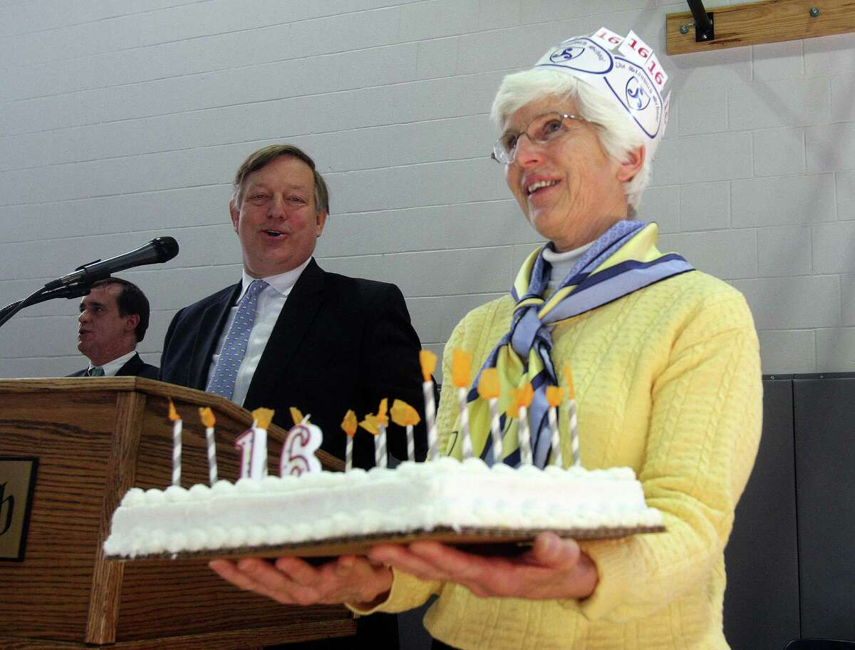 Barrie Richmond of the Stanwich School shows off a birthday cake to students and teachers at an assembly to mark its 16th anniversary as a school on Friday, Jan. 24, 2014, in Greenwich, Conn. Joining in the celebration is Paul Geise, Head of School.