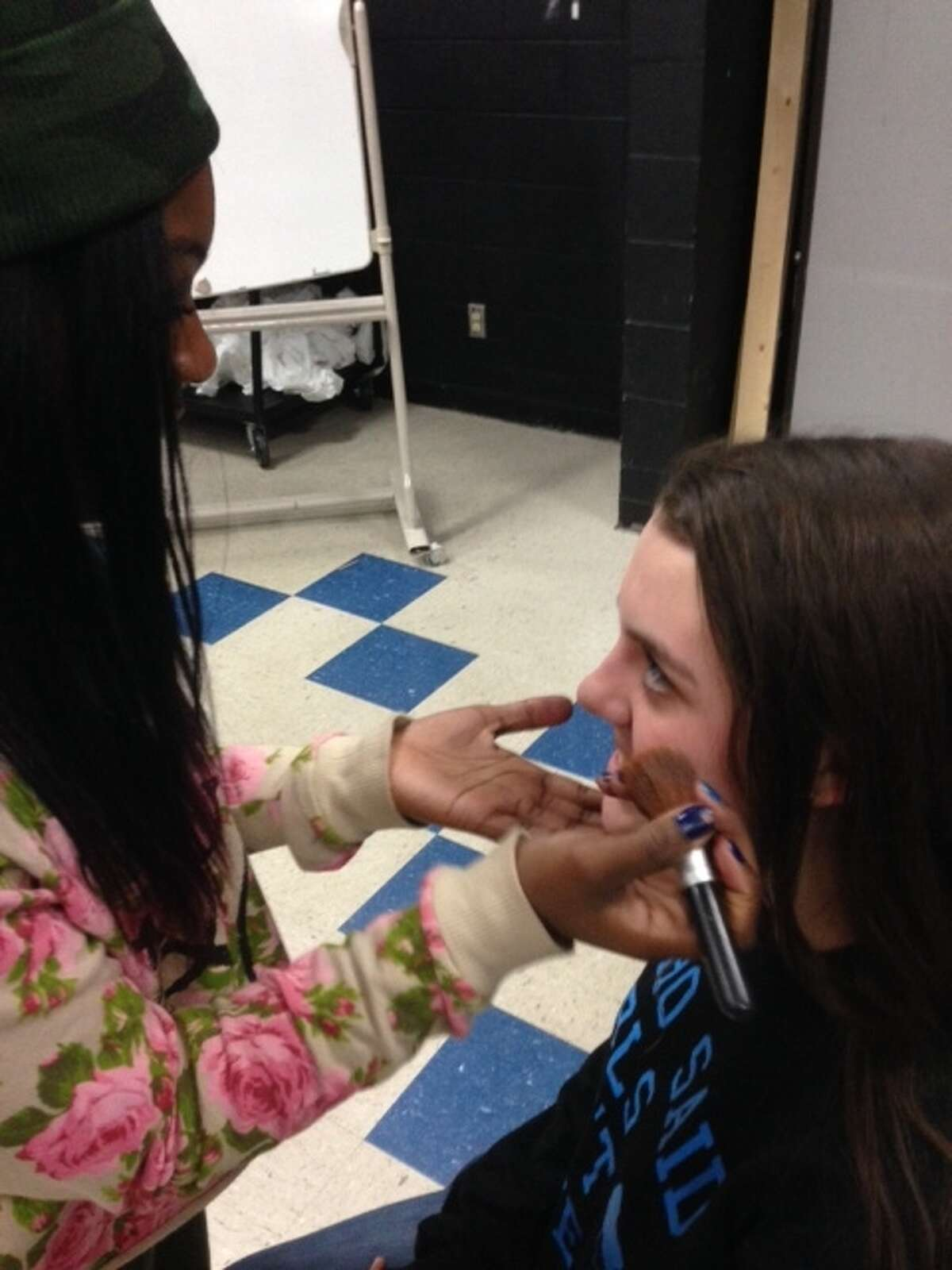 Kelly Howland practices make-up techniques before applying it to the actors in the cast of