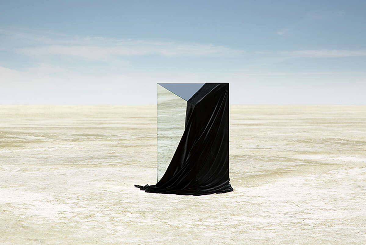 """A still image from the second part of Anton Ginzberg's """"Terra Corpus,"""" on view for the first time at the Blaffer Art Museum. Its wandering character wears a mirror-like sculpture like a backpack that reflects his surroundings."""